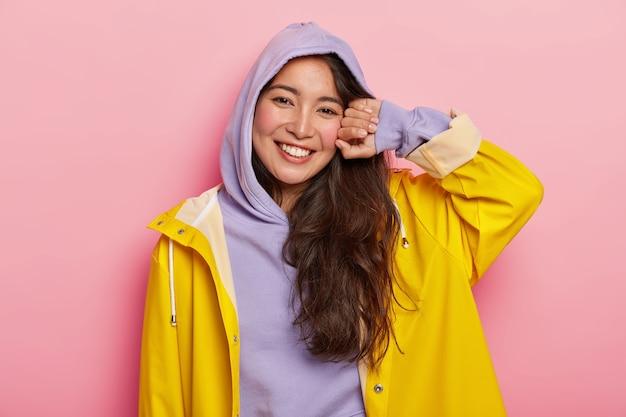 Pozytywna brunetka kobieta w swobodnej bluzie z kapturem i płaszczu przeciwdeszczowym, uśmiecha się przyjemnie, będąc w dobrym nastroju po spacerze na świeżym powietrzu z chłopakiem