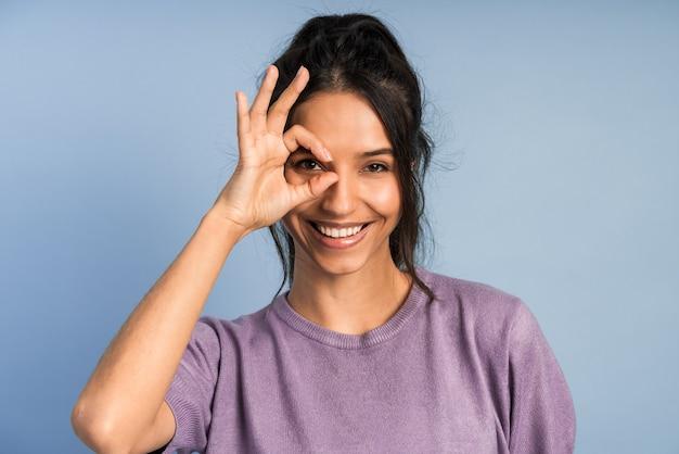 Pozytywna brunetka pokazuje znak w porządku, przykłada palce do oczu. śliczna dziewczyna gestykuluje.