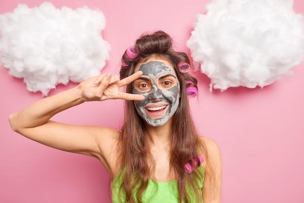 Pozytywna brunetka uśmiecha się delikatnie, wykonując gest pokoju nad oczami, nakłada glinianą maskę, aby zredukować drobne linie i zaskórniki, tworząc idealną fryzurę w domu w pozach w domu na różowej ścianie