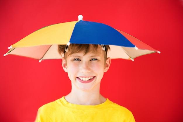 Pozytywna chłopiec pod kolorowym parasolem. pojęcie ochrony i prognozowania