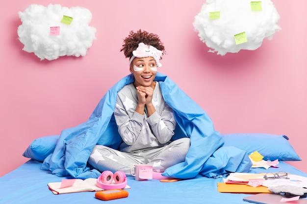 Pozytywna ciekawa kręcona dziewczyna w piżamie trzyma ręce pod brodą, radośnie patrzy na bok, zapisuje pozostałe notatki