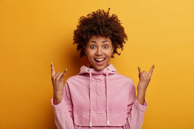 Pozytywna ciemnoskóra kobieta robi rockowy znak, demonstruje rock-n-rollowy gest