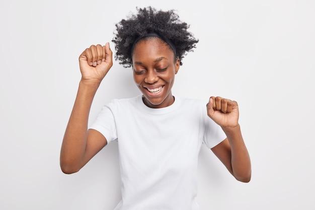 Pozytywna ciemnoskóra kobieta tańczy beztrosko unosi ramiona w rytm ulubionej muzyki