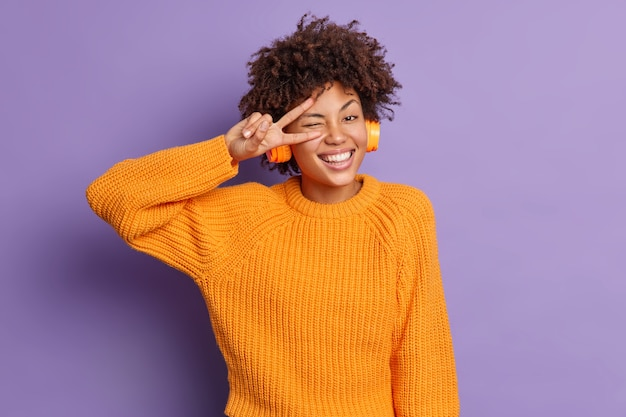 Pozytywna ciemnoskóra kobieta wykonuje gest pokoju ponad oczami uśmiecha się szeroko bawi się dobrze czuje się rozbawiona słucha przyjemnej piosenki w pozach słuchawek