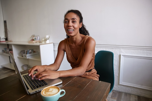 Pozytywna ciemnoskóra kobieta z kręconymi włosami pracująca zdalnie w kawiarni, trzymając ręce na breloczku i patrząc radośnie
