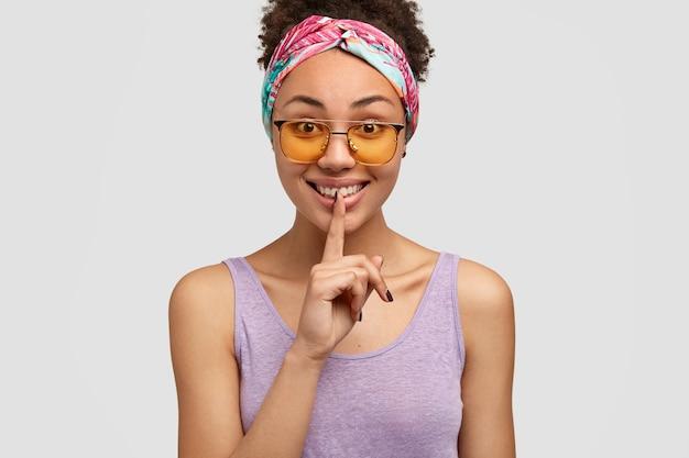 Pozytywna ciemnoskóra młoda kobieta daje znak ciszy