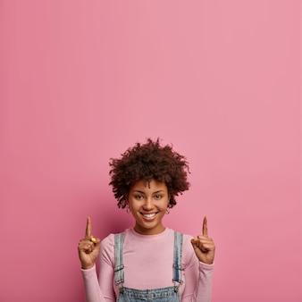Pozytywna ciemnoskóra młoda kobieta wskazuje palcem wskazującym powyżej
