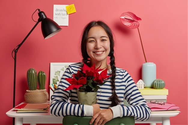 Pozytywna ciemnowłosa dziewczyna trzyma czerwony kwiat w doniczce, pozuje na tle przytulnej przestrzeni coworkingowej