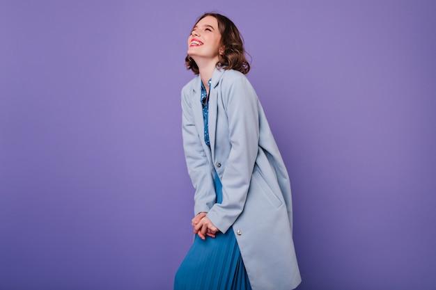 Pozytywna ciemnowłosa dziewczyna uśmiechnięta podczas sesji zdjęciowej w niebieskim płaszczu. niesamowita kręcona kobieta wyrażająca pozytywne emocje na fioletowej ścianie.