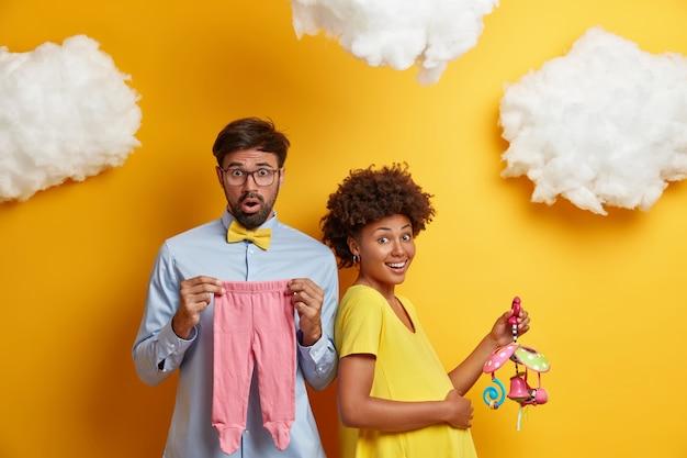 Pozytywna ciężarna samica dotyka brzucha i cofa się do męża, trzyma przedmioty dla nienarodzonego dziecka, szczęśliwa, że wkrótce zostanie rodzicem, spodziewa się pierwszego dziecka, kup wszystkie niezbędne rzeczy przed porodem