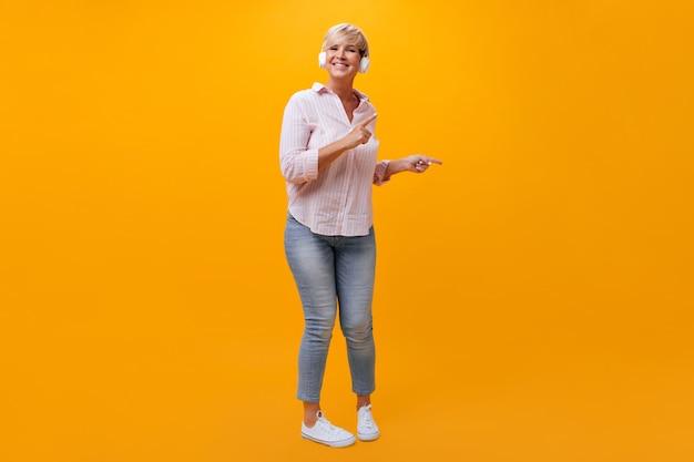 Pozytywna dama w dżinsach i koszuli tańczy i słucha muzyki w słuchawkach