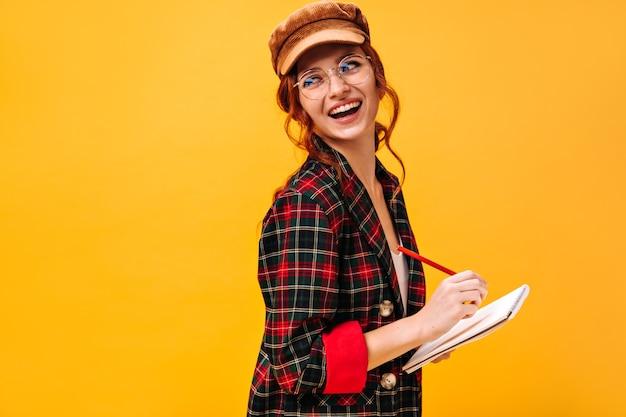 Pozytywna dama w stroju w kratę i czapce pozuje z notatnikiem na izolowanej ścianie