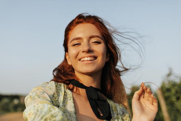 Pozytywna dama z piegami, rudą fryzurą i ciemnym bandażem na szyi uśmiecha się w stylowej sukience i robi selfie na świeżym powietrzu