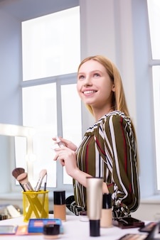 Pozytywna, dobrze wyglądająca młoda kobieta uśmiecha się, ciesząc się swoim pięknem