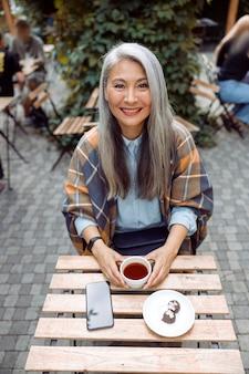 Pozytywna dojrzała azjatycka kobieta z filiżanką cukierków herbacianych i telefonem komórkowym siedzi na tarasie kawiarni na świeżym powietrzu