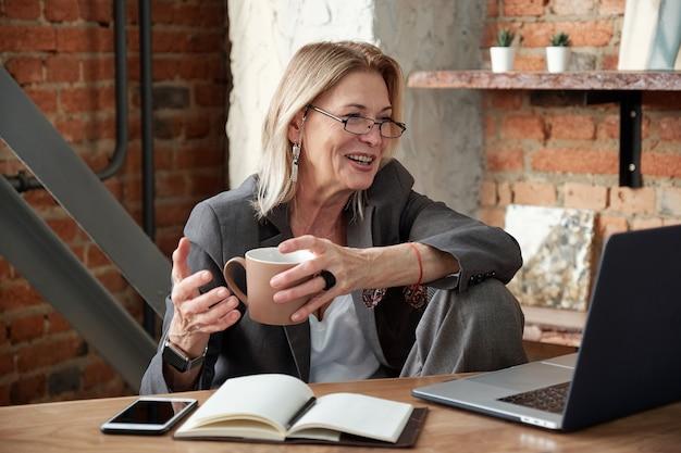 Pozytywna dojrzała kobieta w okularach siedzi we własnym biurze i pije kawę podczas komunikowania się z kolegą za pośrednictwem aplikacji na laptopa