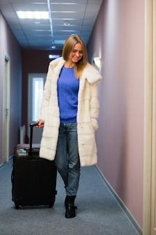 Pozytywna dorosła kobieta stoi w sala z pakowanym bagażem