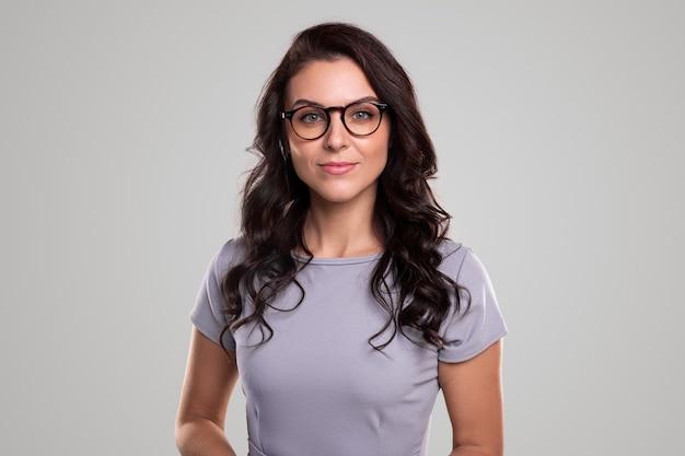 Pozytywna dorosła kobieta w swobodnym stroju i stylowych okularach uśmiecha się i patrzy na kamerę na szarym tle