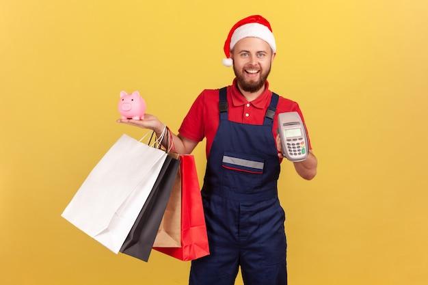 Pozytywna dostawa mężczyzna w mundurze i czapce świętego mikołaja trzymający papierowe torby na zakupy, terminal płatniczy i skarbonkę, płacący zbliżeniowo i oszczędzający pieniądze, zwrot gotówki. kryty na białym tle na żółtym tle