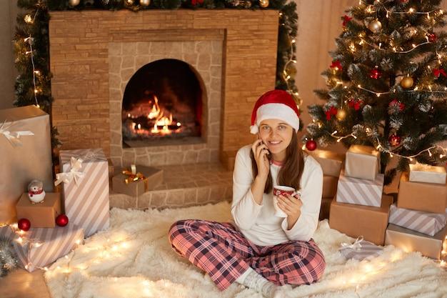 Pozytywna dziewczyna ciesząca się świąteczną atmosferą wakacji, używając smartfona do rozmowy