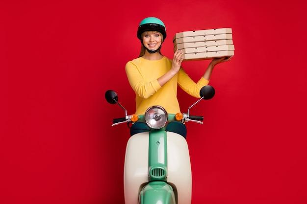 Pozytywna dziewczyna dziewczyna kierowca roweru kurier trzymać stosu pizzy na czerwonej ścianie