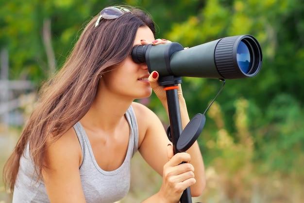 Pozytywna dziewczyna oglądająca w lunetę podczas chodzenia