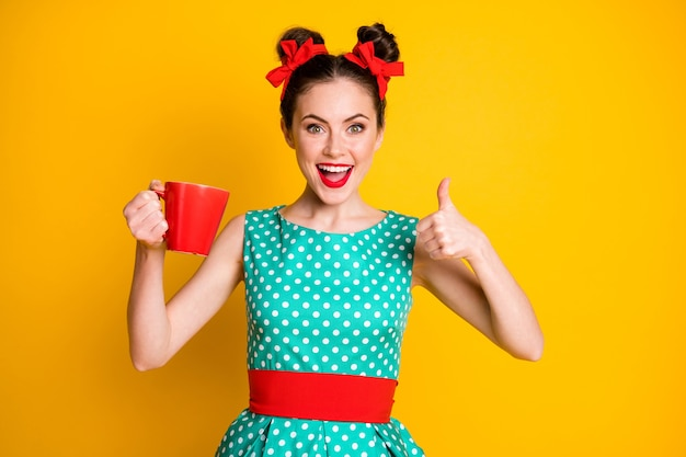 Pozytywna dziewczyna pokazuje kciuk w górę znak kubek do napojów kofeiny nosić turkusową spódnicę na białym tle połysk kolor tła
