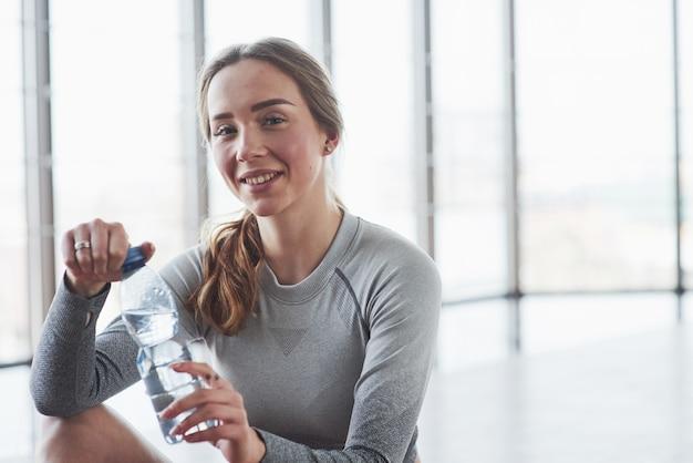 Pozytywna dziewczyna robi sobie przerwę. sportive młoda kobieta ma dzień fitness na siłowni w godzinach porannych