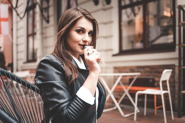 Pozytywna dziewczyna siedzi na ulicy przy stoliku w kawiarni i pali elektroniczny papieros.