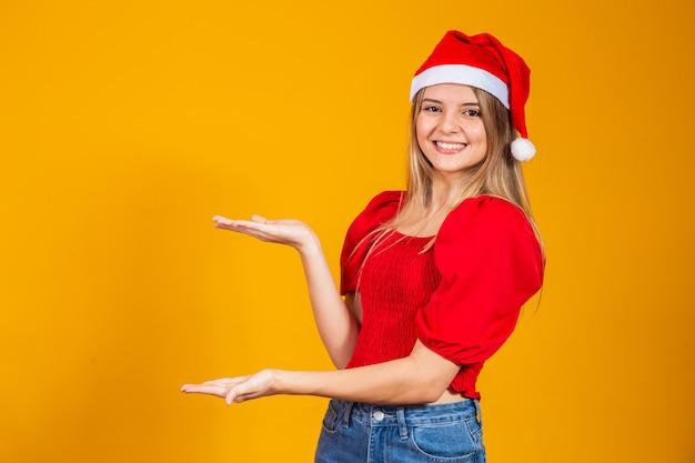 Pozytywna dziewczyna w santa kapeluszu, wskazując na przestrzeń tekstu. promocja i reklamy na białym tle na żółtym tle.