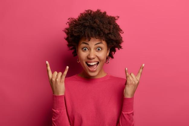 Pozytywna dziewczyna z kręconymi włosami wykonuje gest klaksonu, lubi muzykę rock and roll, śmieje się z radości, nosi swobodny sweter