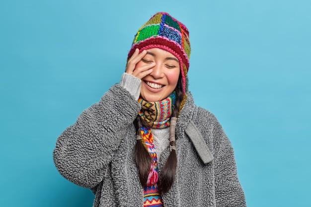 Pozytywna dziewczyna ze wschodu z dwoma warkoczykami sprawia, że twarz dłoni się uśmiecha, a oczy są zamknięte