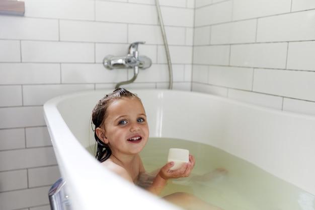 Pozytywna dziewczynka siedzi w wodzie wanny z mydłem w kostce podczas mycia w wannie