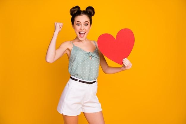 Pozytywna ekstatyczna dziewczyna dostaje duże czerwone papierowe serce serce podnosi pięści krzyczeć na białym tle