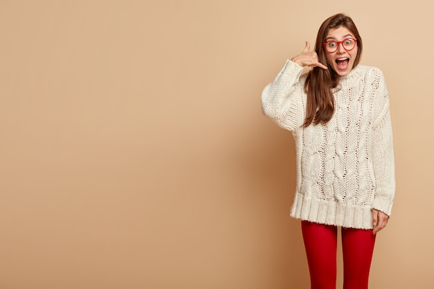 """Pozytywna emocjonalnie modelka trzyma palce w geście """"zadzwoń do mnie"""", nosi przezroczyste okulary, biały sweter"""