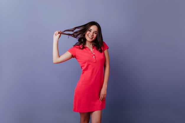 Pozytywna europejska dziewczyna zabawy w pomieszczeniu. wyrafinowana brunetka dotykająca włosów podczas sesji zdjęciowej na fioletowej ścianie.