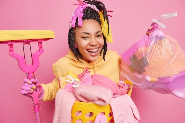 Pozytywna gospodyni domowa z dredami uśmiecha się szeroko zbiera śmieci