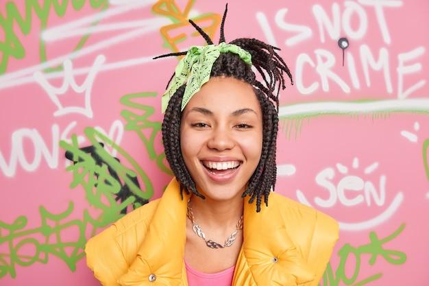 Pozytywna hipsterka uśmiecha się szeroko i lubi spędzać wolny czas w pozach na kolorowej ścianie graffiti, ubrana w swobodne ubrania w stylu ulicznym, będąc w dobrym nastroju