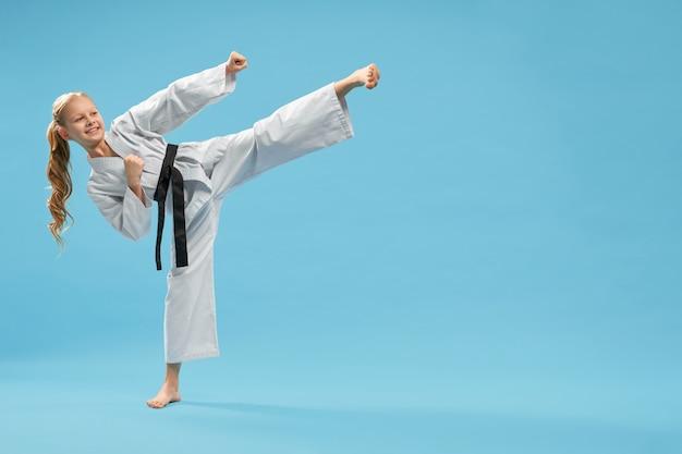 Pozytywna karate dziewczyna ćwiczy kopnięcie stopę do przodu.