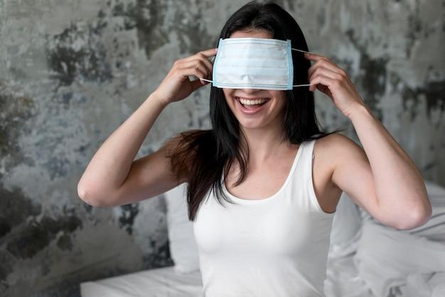 Pozytywna kobieta bawić się z twarzy maską