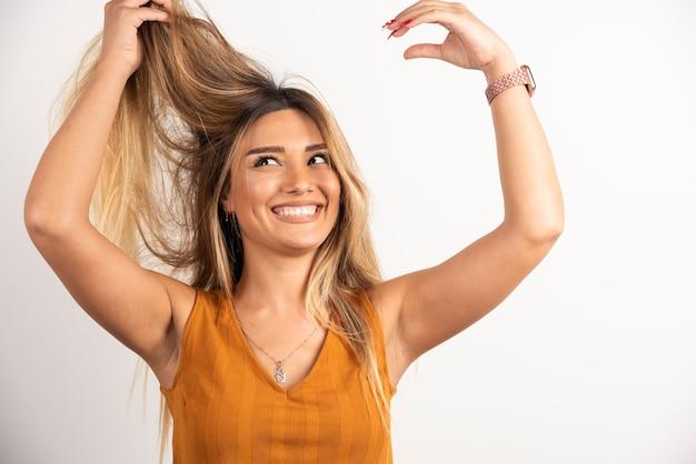 Pozytywna kobieta dotyka jej włosów i pozowanie na białym tle.