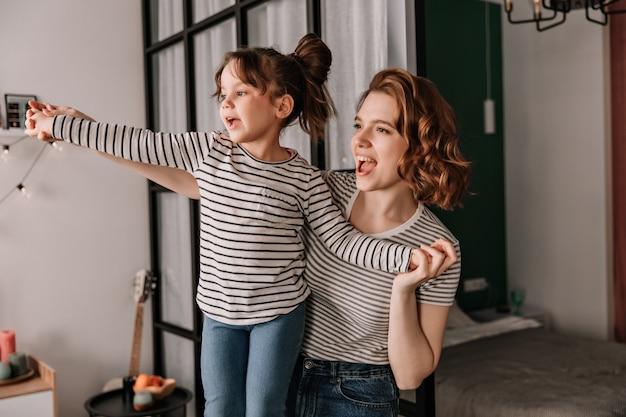 Pozytywna kobieta i jej córka w pasiastych koszulkach śmieją się i tańczą w mieszkaniu.