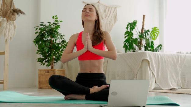 Pozytywna kobieta jogi ćwiczy przed laptopem siedząc na macie sportowej w domu