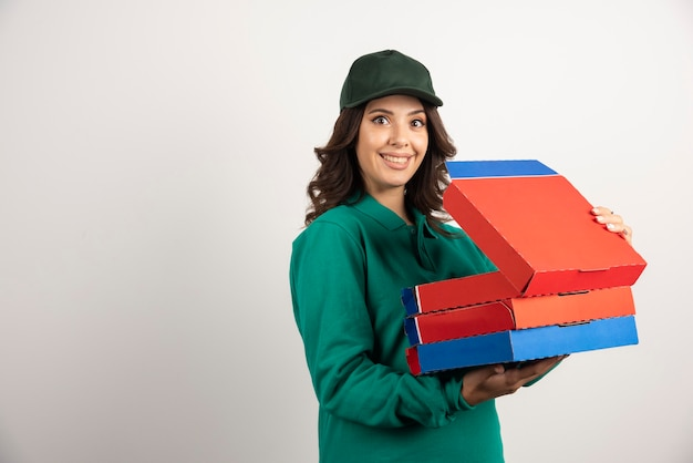 Pozytywna kobieta kurierska trzymająca otwarte pudełko po pizzy.