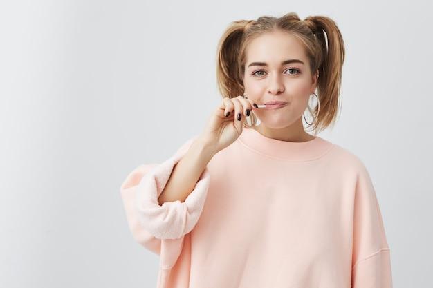 Pozytywna kobieta o śmiesznym wyglądzie, figlarna, ubrana w luźny różowy sweter, z lizakiem w ustach, pozuje. szczęśliwa nastolatka z dwoma ogonami kucyka pokazując pozytywne emocje.