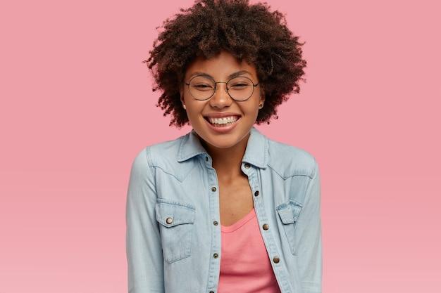Pozytywna kobieta o zdrowej skórze, szerokim uśmiechu, cieszy się życiem, jest w dobrym nastroju po usłyszeniu miłych wiadomości od rozmówcy, nosi przezroczyste okulary, odizolowane na różowej ścianie.