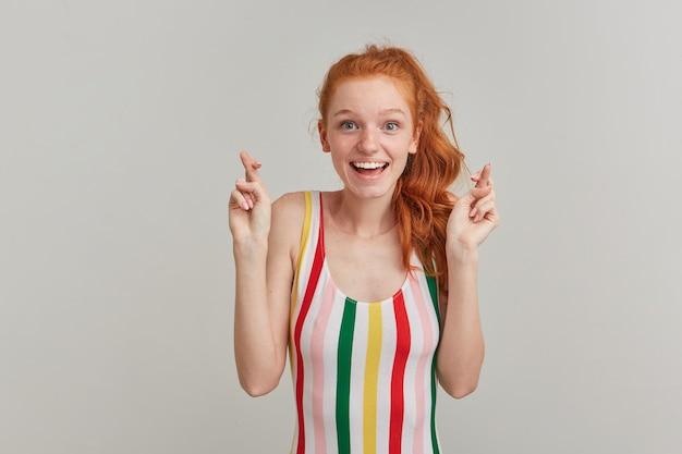 Pozytywna kobieta, piękna ruda dziewczyna z piegami i ogonem kucyka, ubrana w kolorowy strój kąpielowy w paski