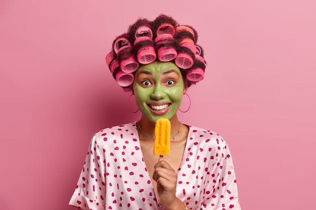 Pozytywna kobieta poddaje się zabiegom kosmetycznym, zjada żółte lody popsicle, nosi lokówki, aby zrobić idealną fryzurę, lubi pyszny zimny deser, nosi szlafrok, pozuje na róż
