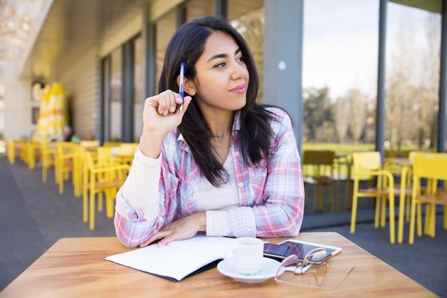 Pozytywna kobieta robi notatkom w plenerowej kawiarni