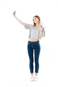 Pozytywna kobieta robi selfie na smartphone